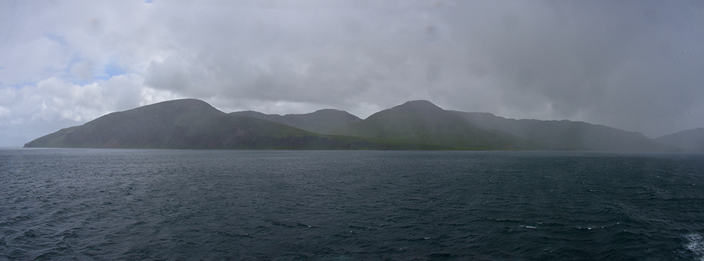 Panoramic picture of some heavy rain over the entrance to a sound between two islands