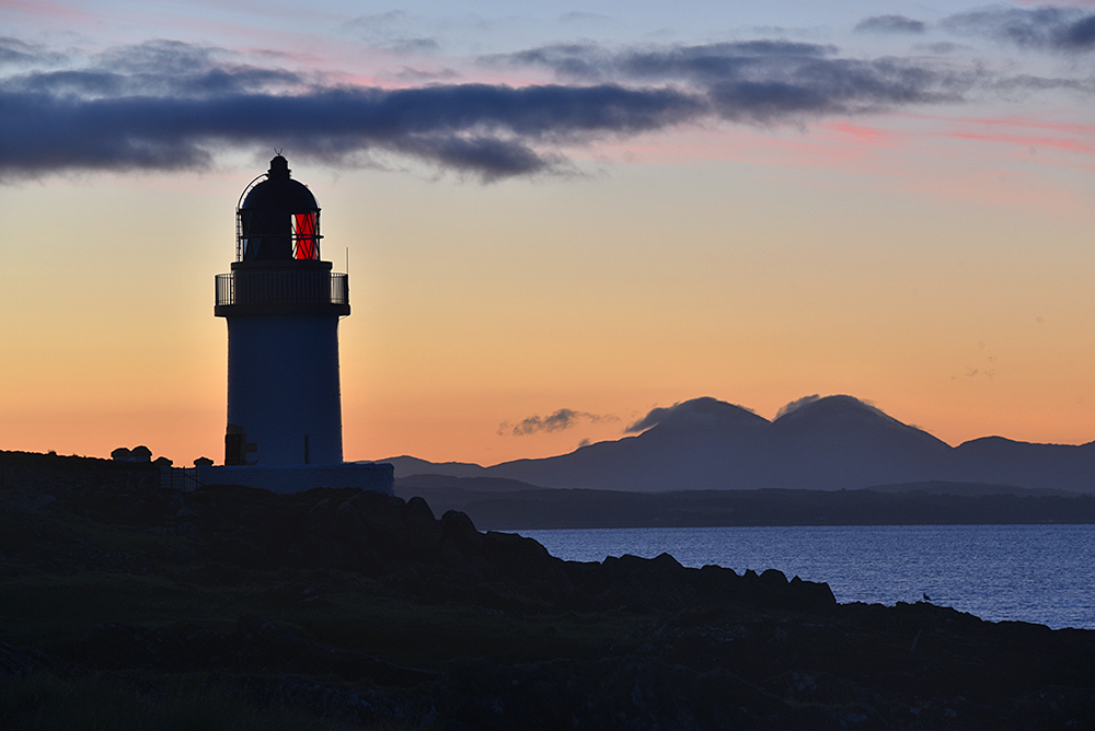 Picture of a small lighthouse at the shore of a sea loch at dawn