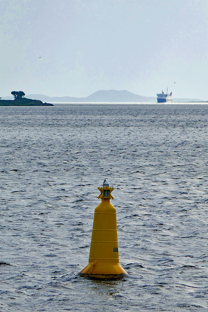 Picture of a ferry entering a sea loch in the distance, a buoy in the foreground