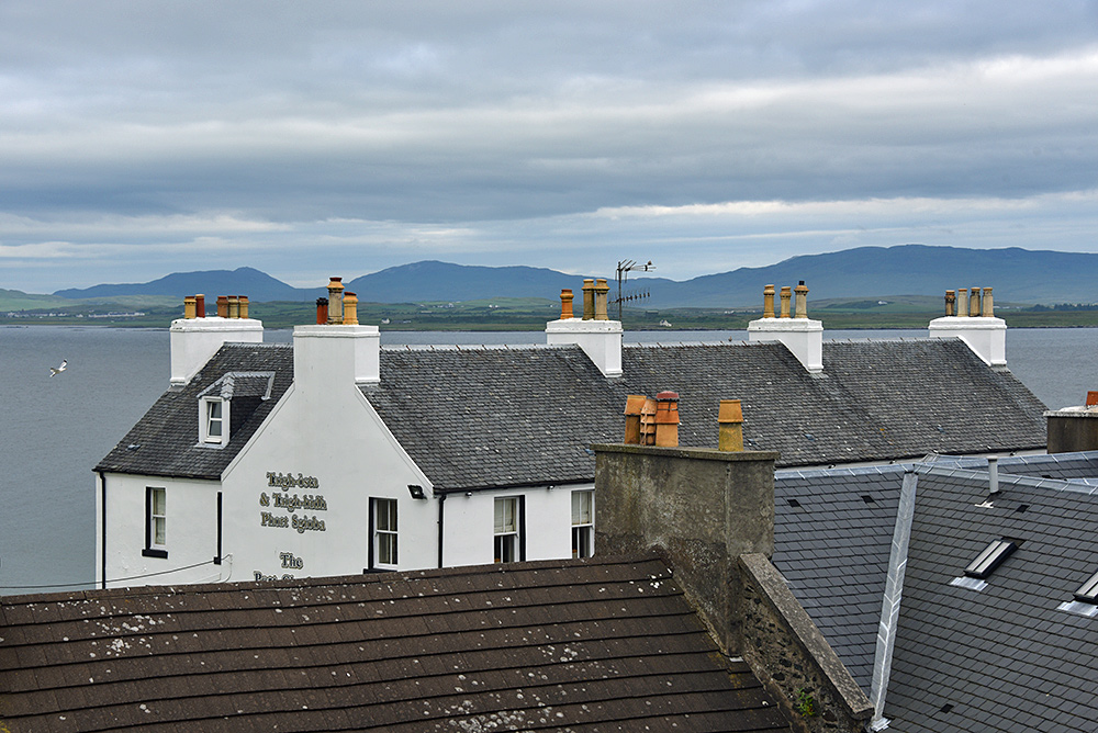Picture of a roof of an old hotel seen across other roofs
