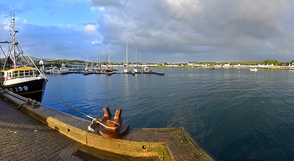 Panoramic picture of a view over a marina and a small loch with a coastal village