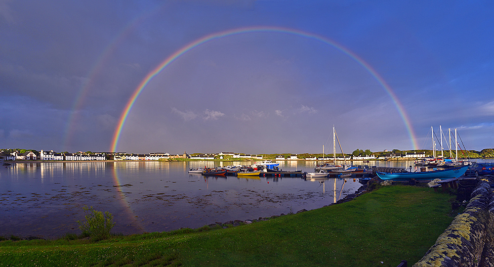 Panoramic picture of a full rainbow over a coastal village with a small marina