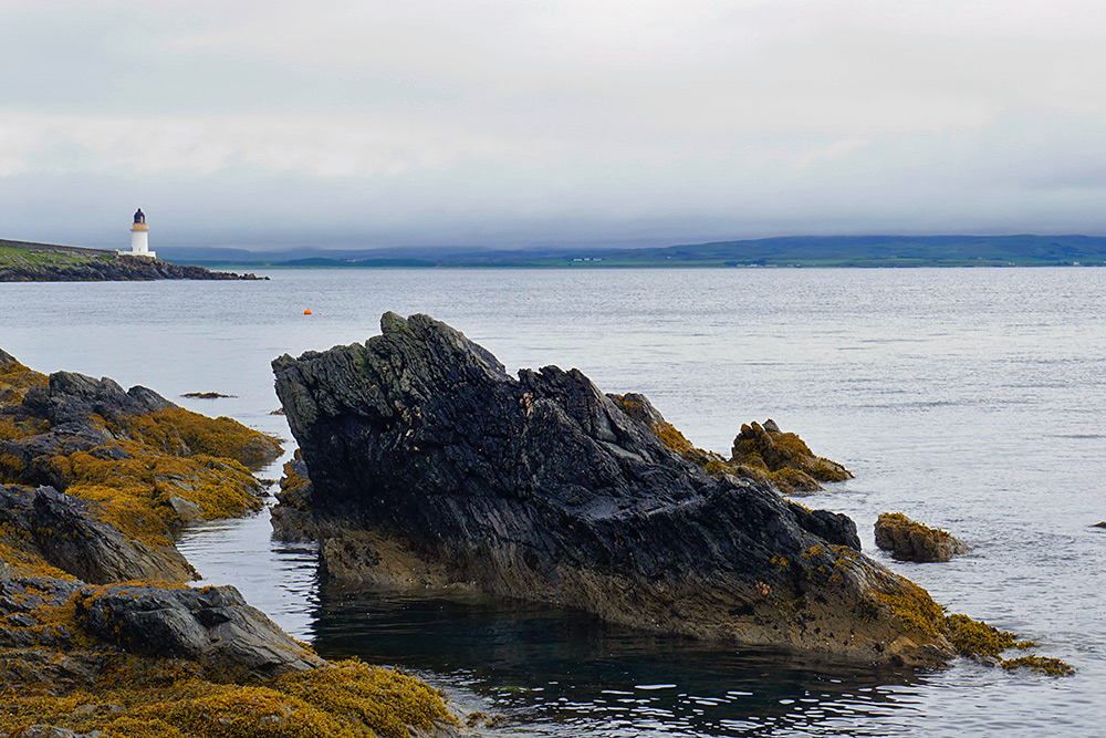Picture of coastal rocks with a small lighthouse in the distance