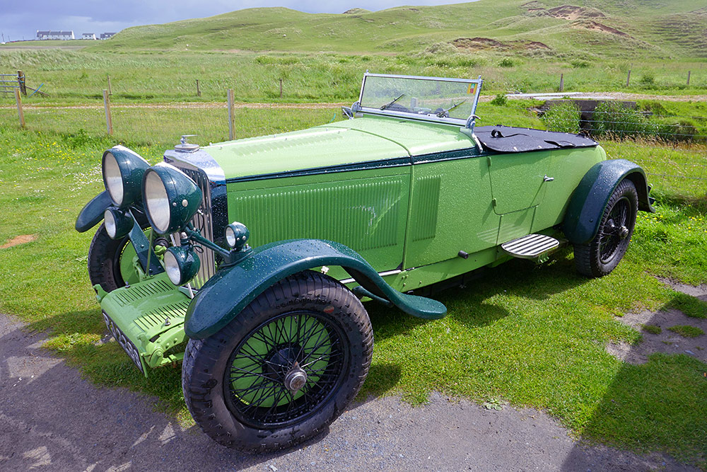 Picture of a green vintage Talbot car parked on a grassy spot