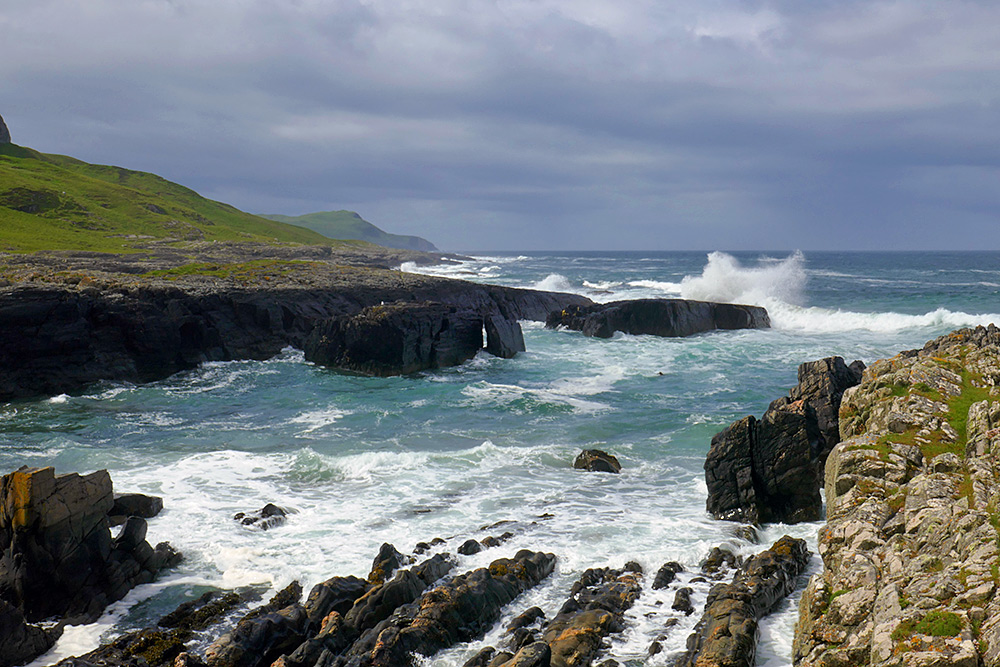 Picture of a rocky shoreline in the sun with dark clouds moving in