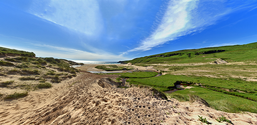 Panoramic picture of a view through dunes to a bay with a beach