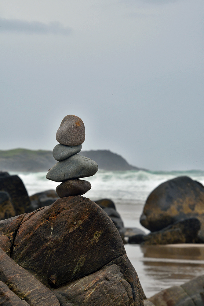Picture of 4 small stones balancing on a large stone
