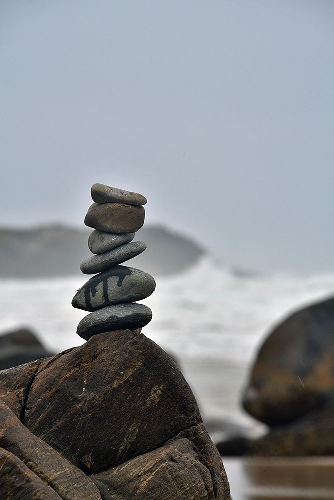 Picture of six stones balancing on a larger rock
