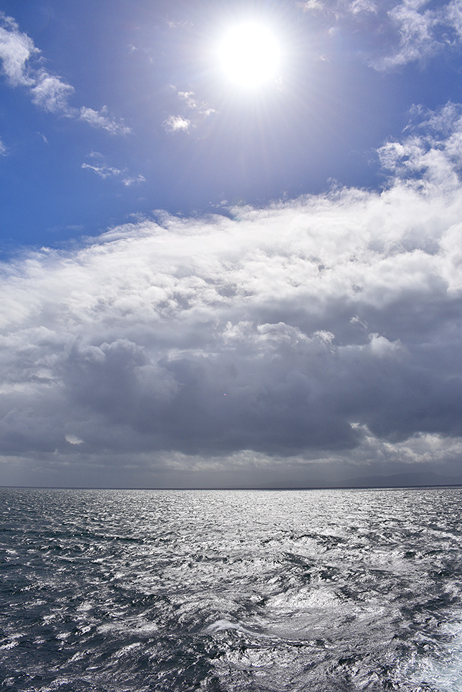 Picture of a bright sun above some dark clouds over the sea