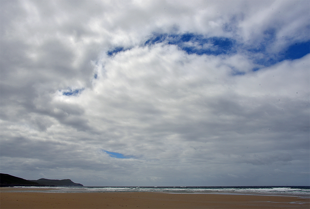 Picture of a break in the clouds over a bay with a sandy beach