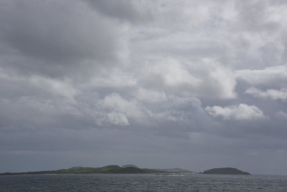 Picture of a small island with low hills under dramatic clouds