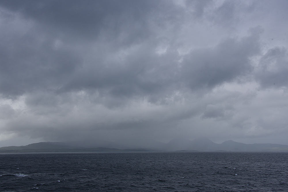 Picture of some very heavy rain falling over an island, seen from a passing ferry