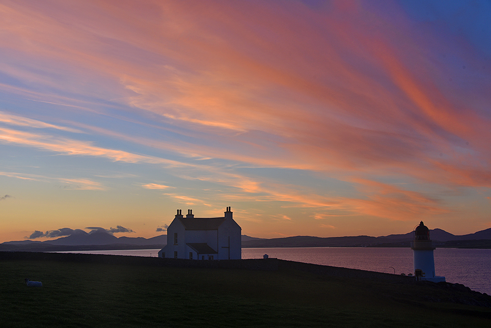 Picture of a June morning dawn at a house and a lighthouse overlooking a sea loch