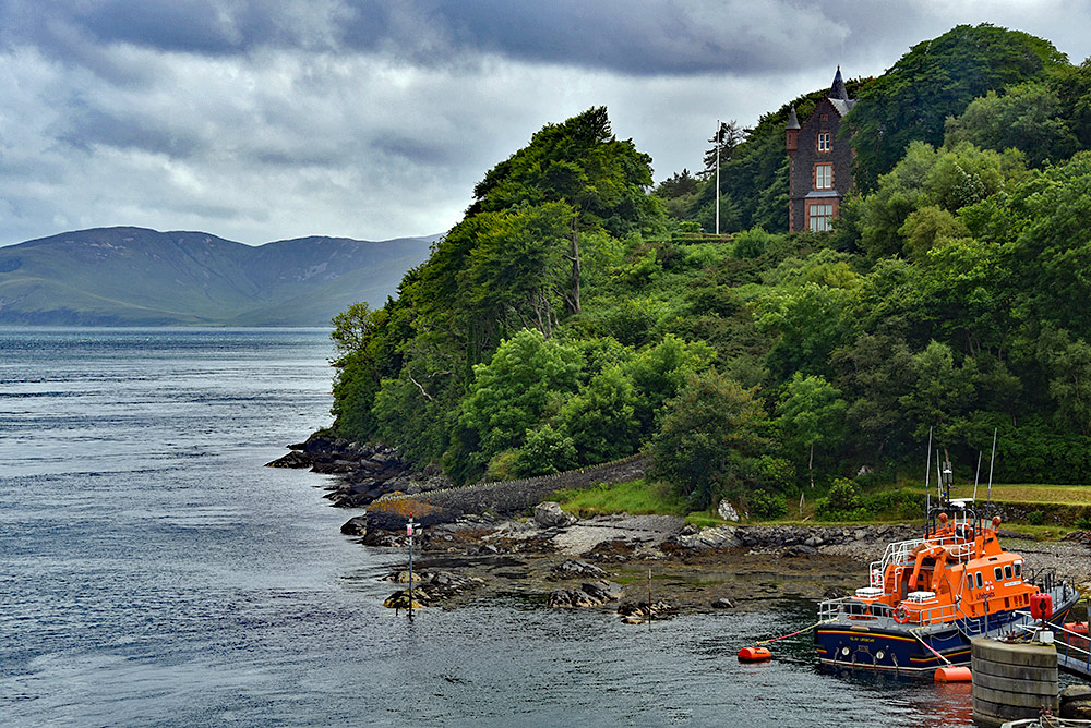 Picture of a RNLI lifeboat at its moorings with an old grand house above it, a sound between two islands stretching into the distance