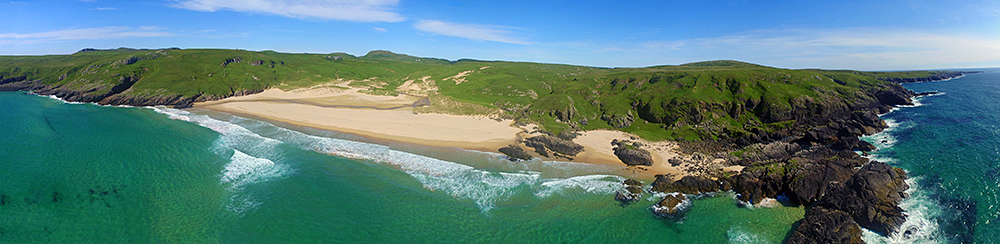 Panoramic picture of a bay with a sandy beach taken from a drone