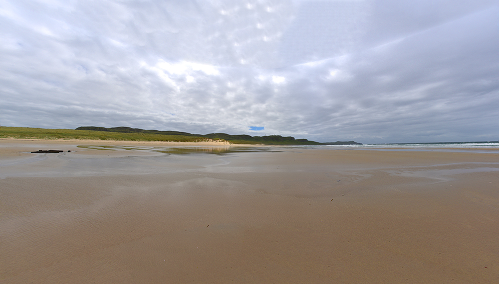 Panoramic picture of a very low tide in a bay with a beach