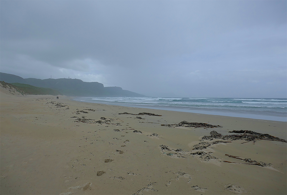Picture of a bay with a sandy beach with heavy rain setting in