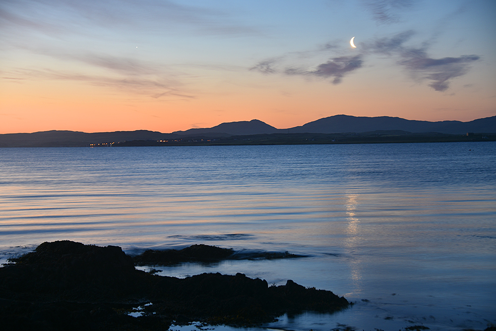 Picture of a June dawn at a sea loch, a crescent Moon visible in the sky