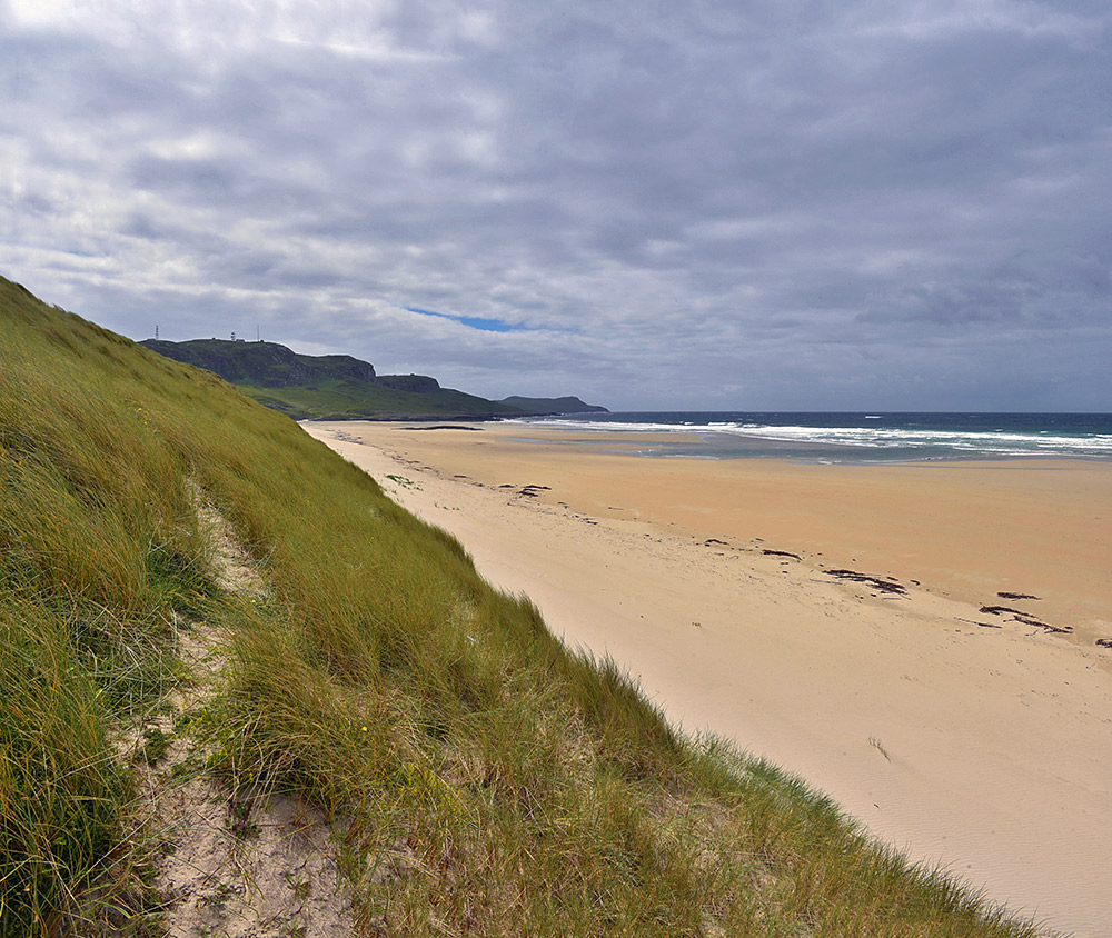 Picture of a view from a dune along a beach on a cloudy day