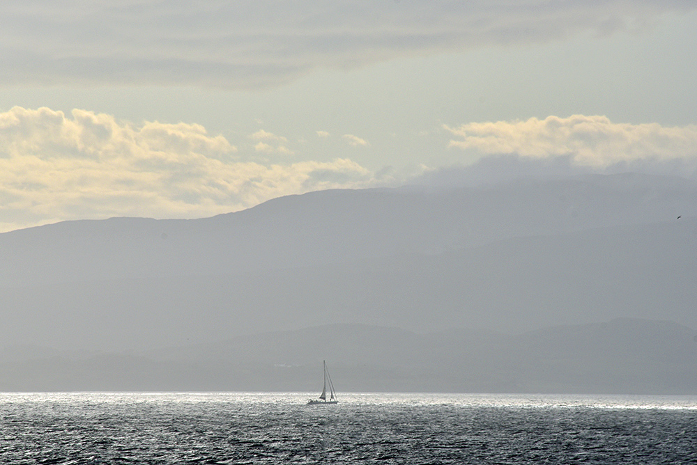 Picture of a sailing yacht passing an island in the hazy evening light