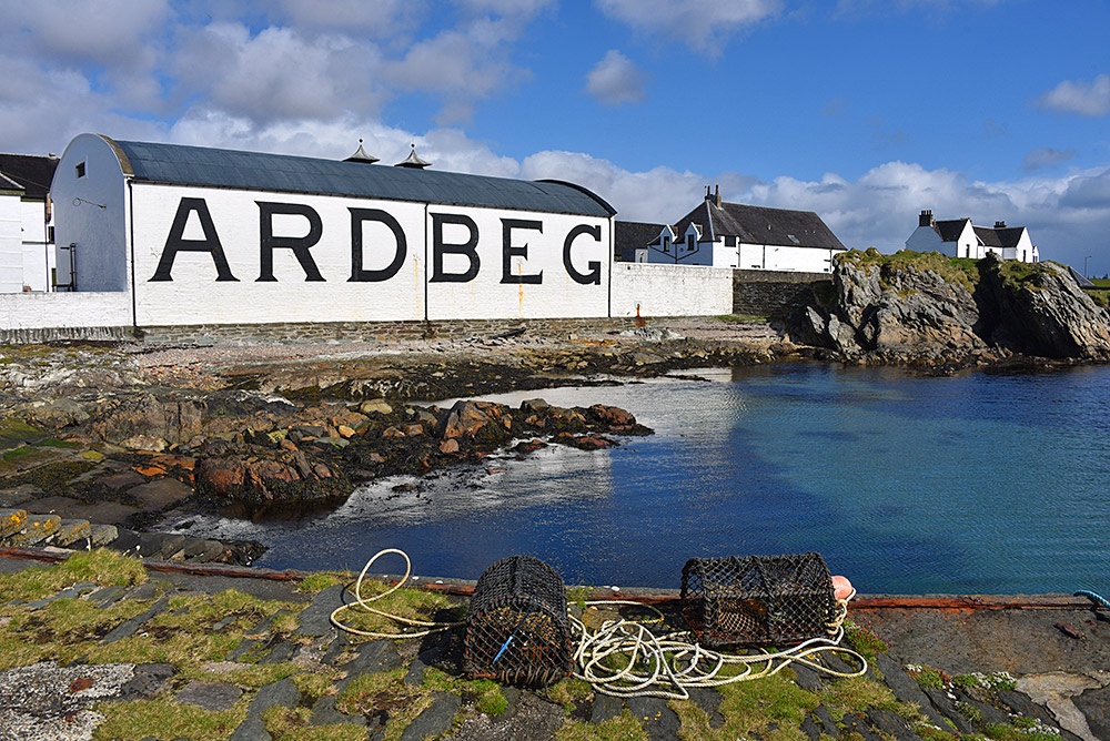 Picture of Ardbeg distillery seen from the pier with some creels on the pier