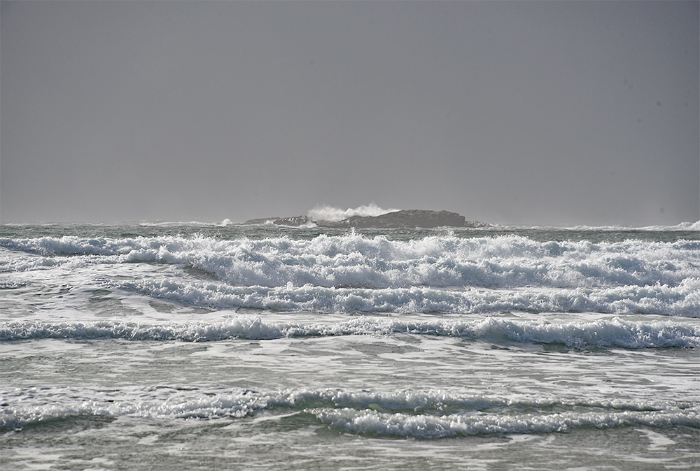 Picture of breaking waves approaching a beach, a small rocky island in the background