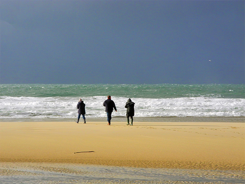 Picture of three people walking on a beach in bright sunshine but dark clouds in the background
