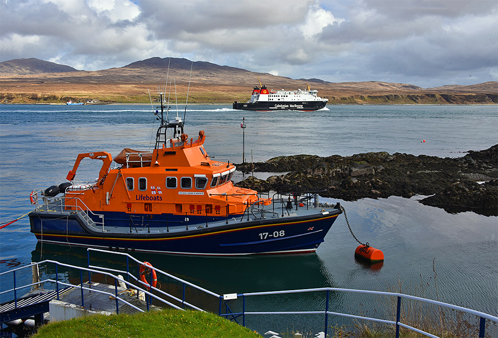 Picture of the Calmac ferry MV Finlaggan passing the moored Islay RNLI lifeboat