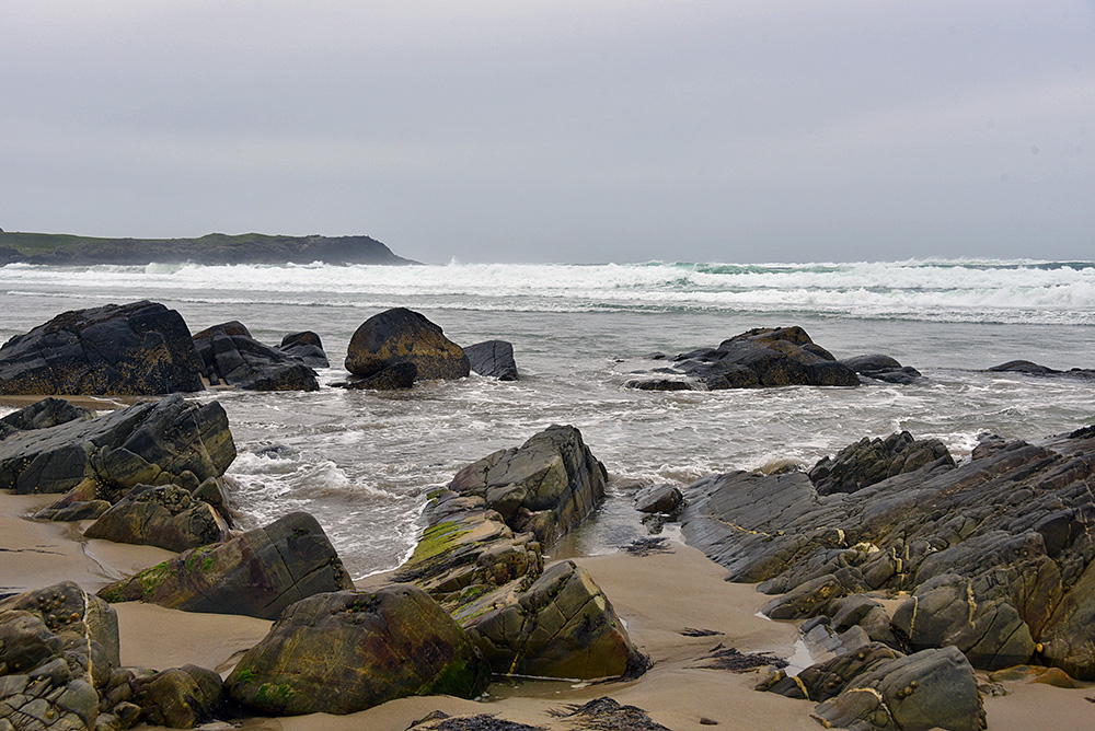 Picture of a wave from an incoming tide rushing in through rocks on a beach