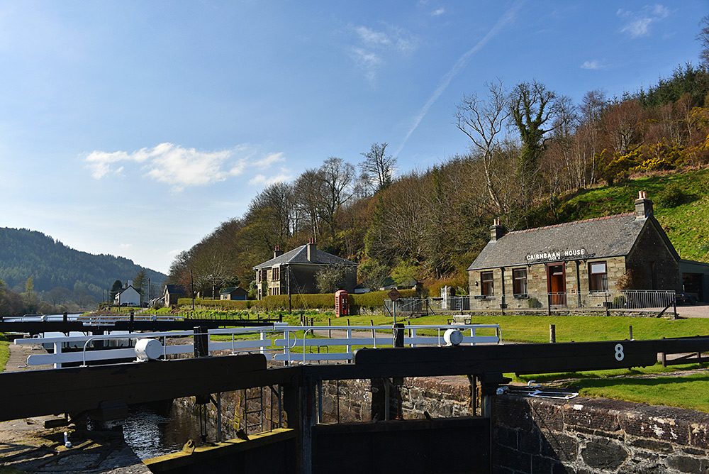 Picture of a canal lock on a sunny April afternoon, a house with a sign Cairnbaan House next to the lock