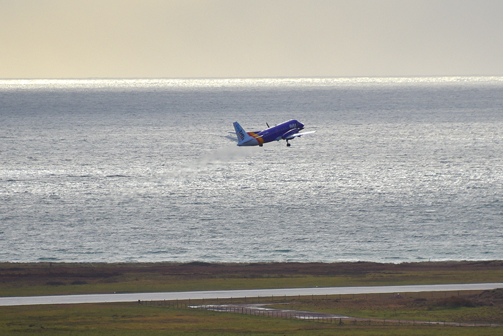 Picture of a small passenger plane departing from a coastal airport