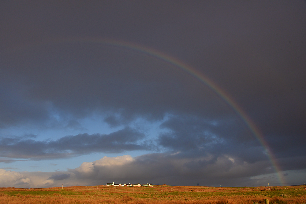 Picture of a rainbow over a small rural settlement