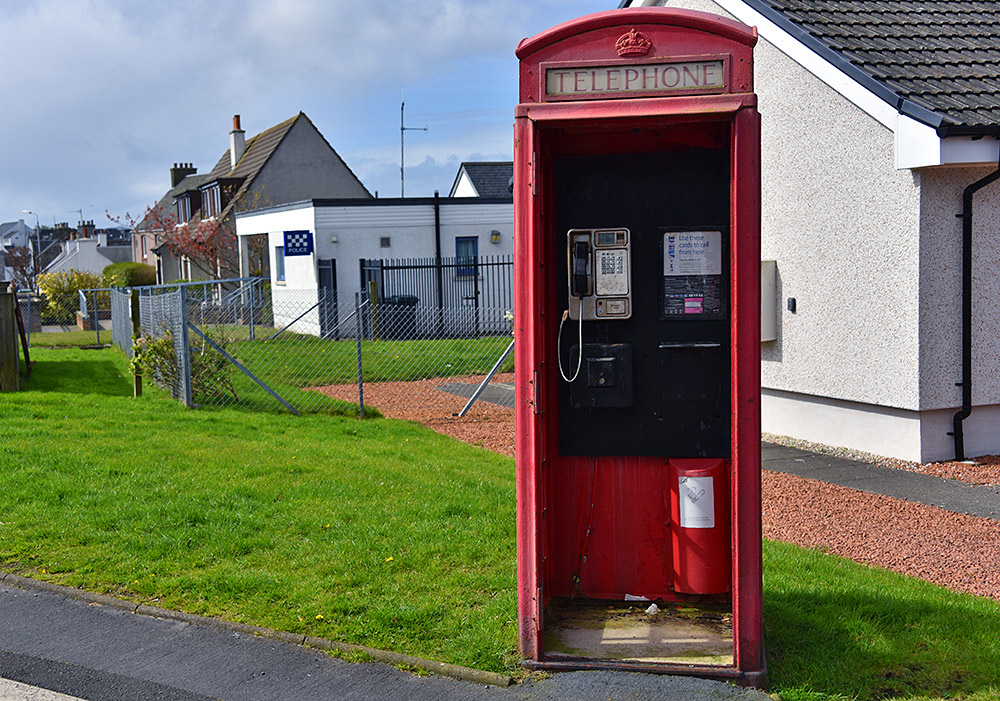 Picture of a red phone box on a road junction, a small police station in the background