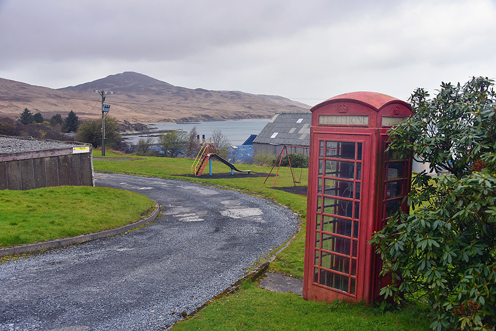 Picture of a red phone box near a playground in a coastal location
