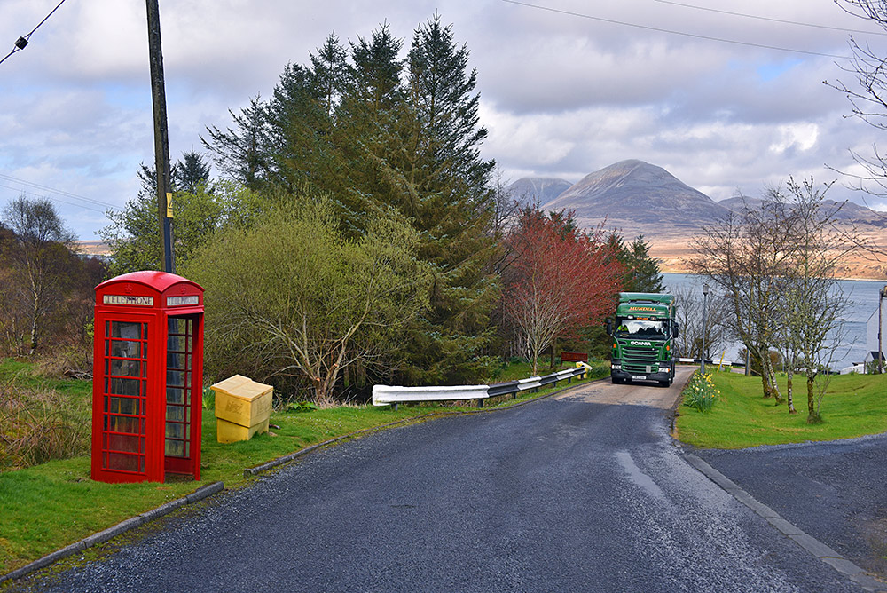 Picture of an old style red phone box at a small road going down a hill to a sound between two islands