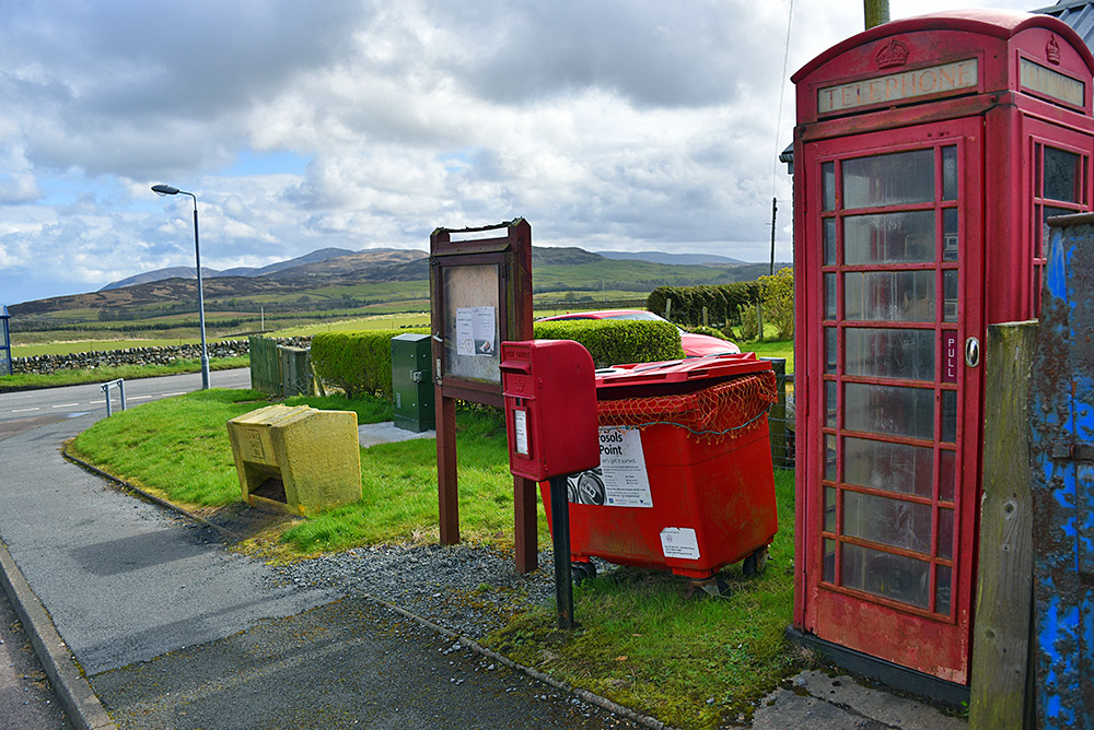 Picture of a red phone box on a road side surrounded by various things