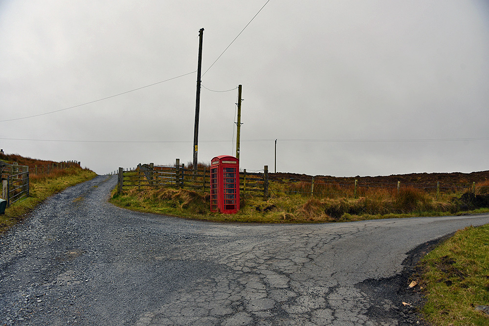 Picture of an old red phone box at a road junction