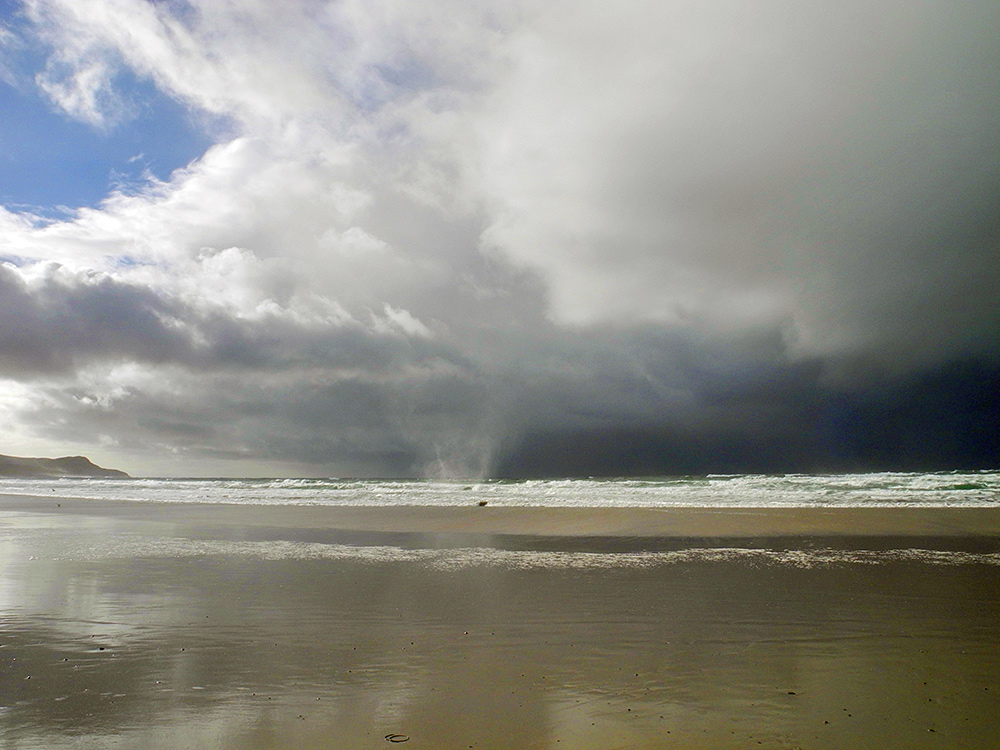 Picture of a faint waterspout approaching a beach