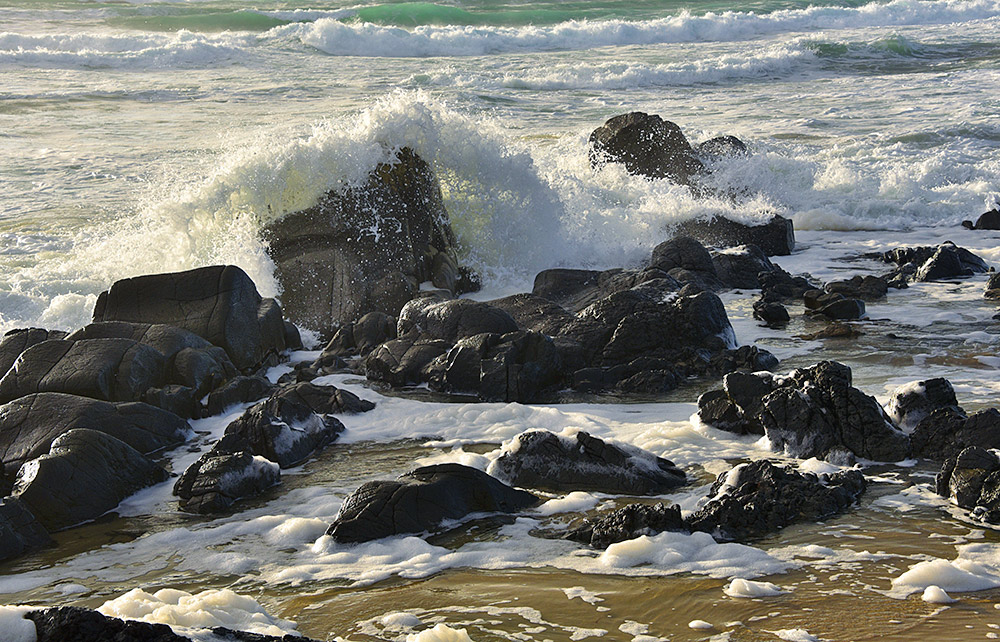 Picture of a wave breaking over a rock on a sandy beach
