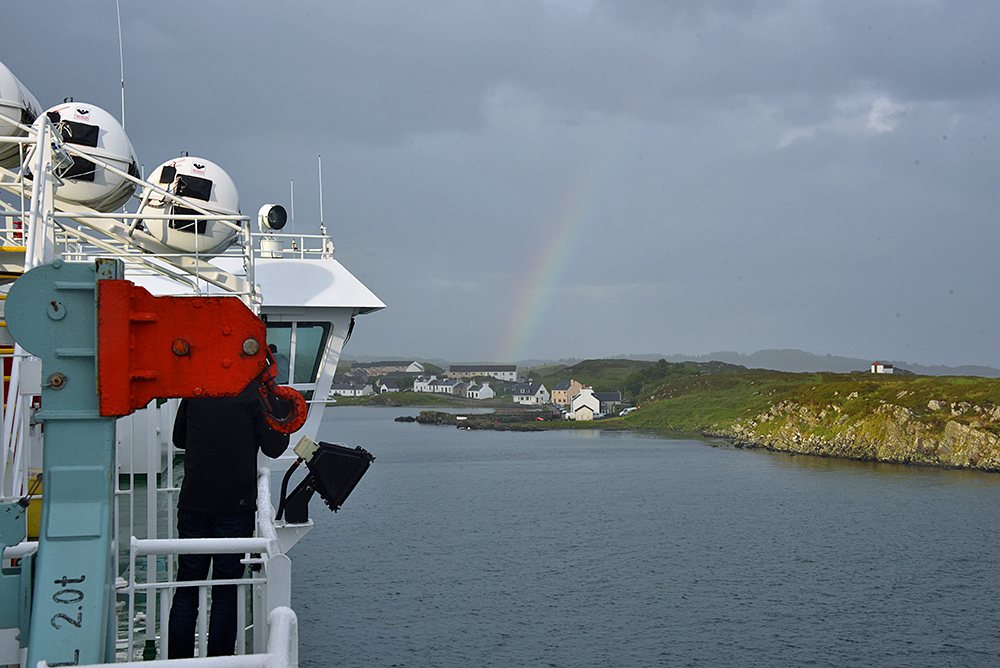 Picture of a view from the top deck of a ferry with a rainbow over a coastal village