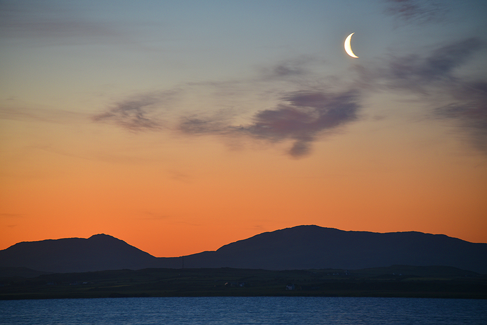 Picture of a crescent Moon at dawn over a range of low hills behind a sea loch