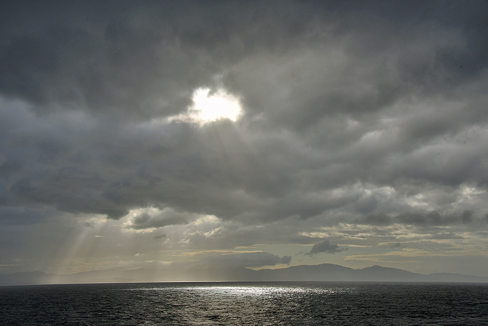 Picture of a dramatic cloudy evening sky with a sunbreak over an island