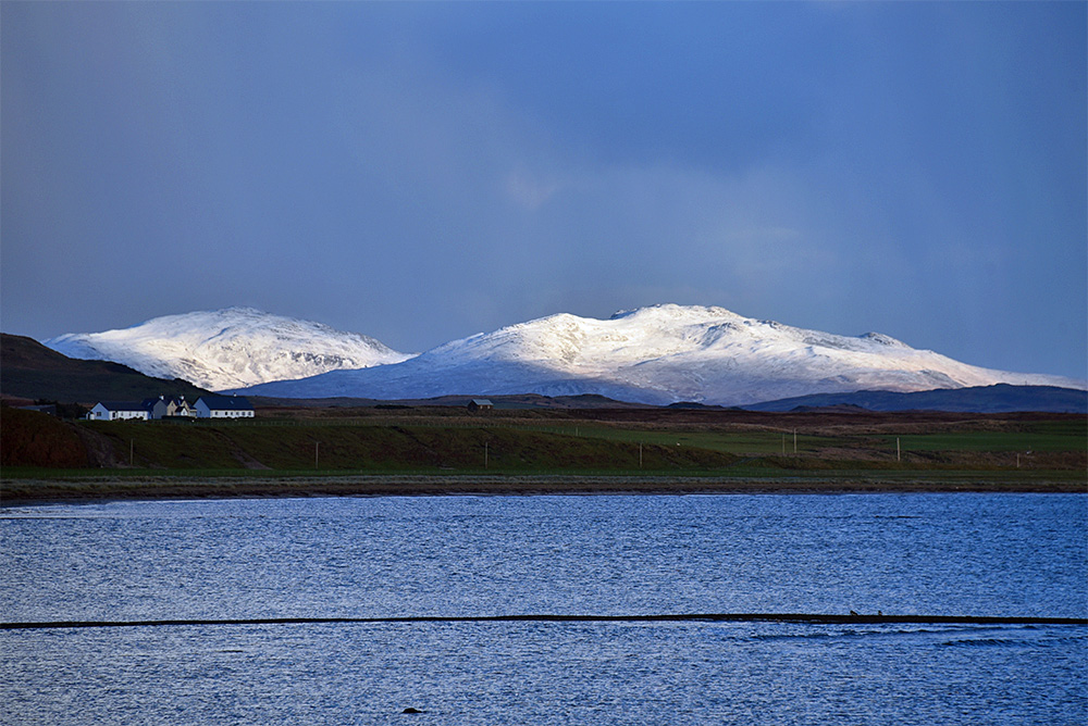 Picture of snow capped hills in the distance, seen across lower hills and a sea loch