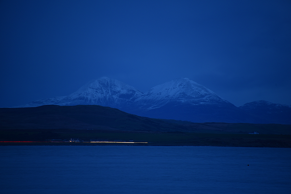 Picture of two snow covered mountains seen across a sea loch