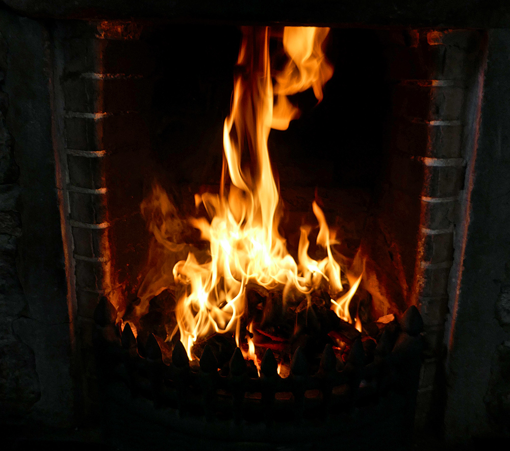 Picture of a roaring open fire in an open fireplace