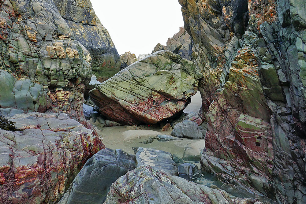 Picture of a view between some steep rocks at the end of a beach