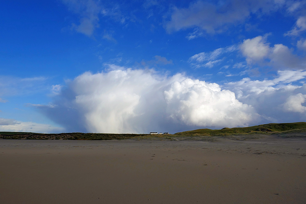 Picture of some large and dramatic clouds above a row of cottages, seen from a beach