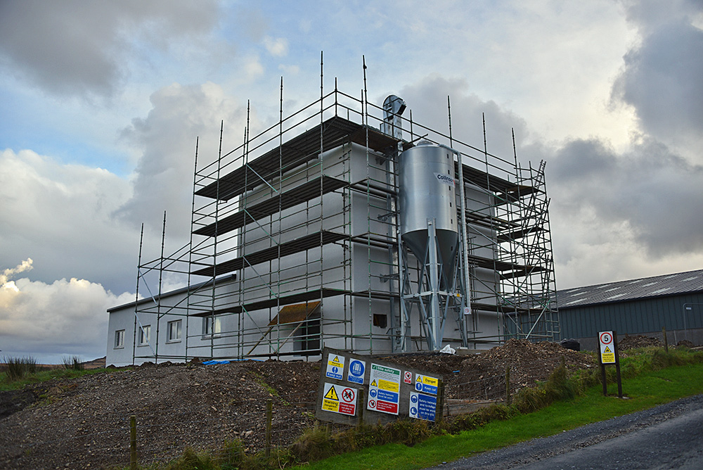 Picture of a distillery building under construction, scaffolding around the building and signs in front of it