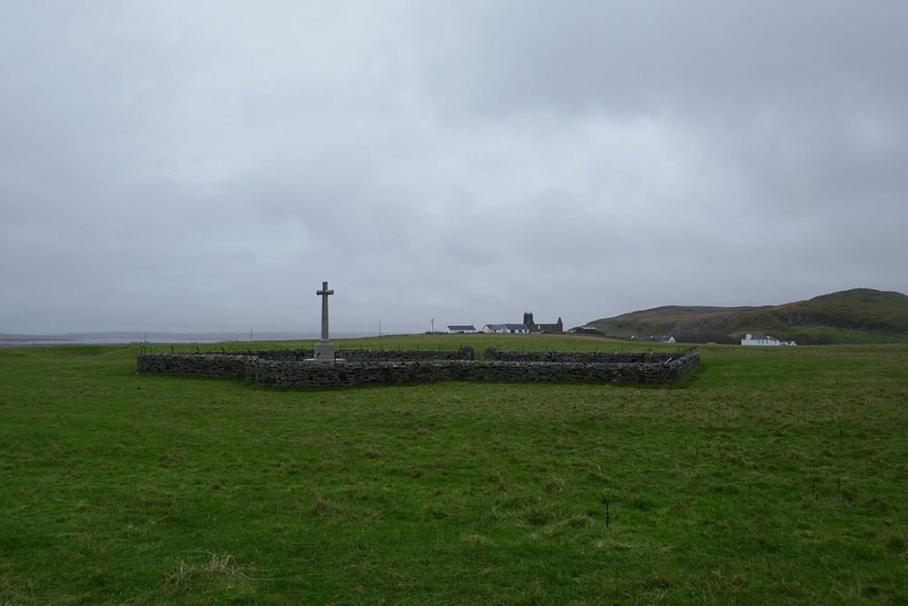 Picture of an old military cemetery/memorial in a field on a rainy day