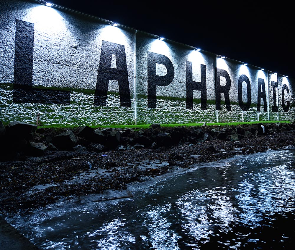 Picture of a Laphroaig distillery warehouse illuminated by downlights at night